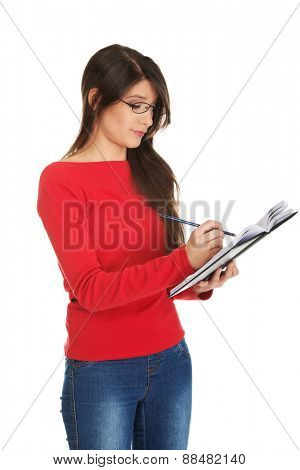 Female student writing a note in her notebook.