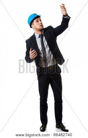 Businessman engineer in hard hat showing copyspace.