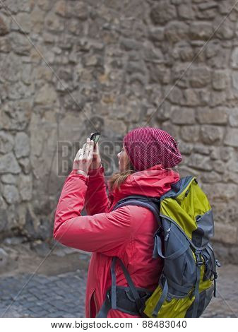 A Young Girl With A Backpack Taking Pictures Of The Phone.