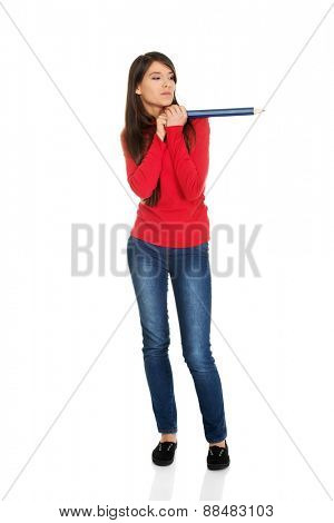 Beautiful young student woman with a big pencil.