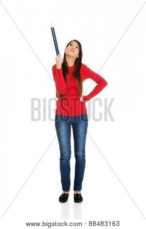 Beautiful student woman pointing up with a big pencil.