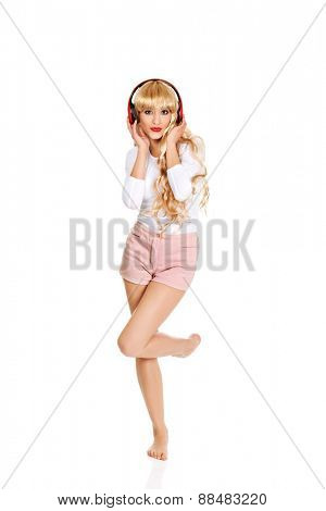 Happy blonde woman dancing and listening to the music.