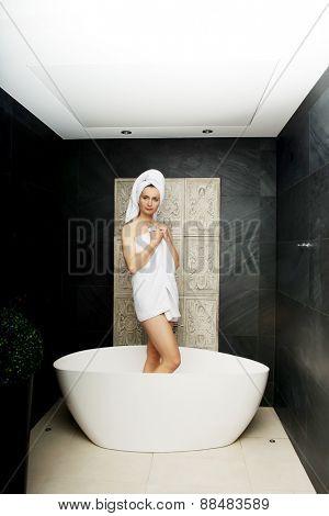 Woman wrapped in towel sitting in bathtub in bathroom.