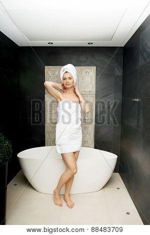 Woman wrapped in towel standing near bathtub in bathroom.