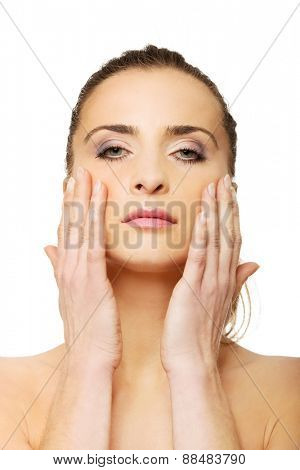 Sensual spa woman with make up touching her face.