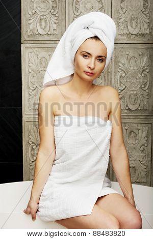 Woman wrapped in towel sitting on bathtub in bathroom.