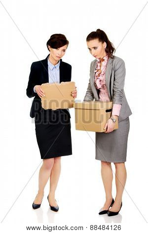 Two fired businesswoman with a box and piece of carton.