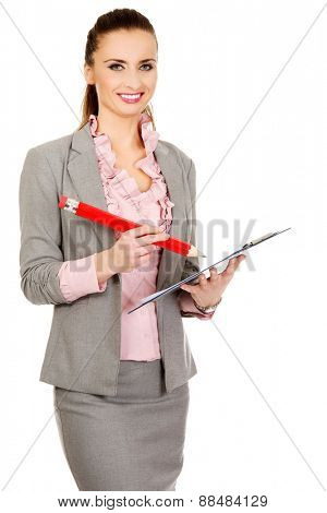 Happy businesswoman writing with big pencil.
