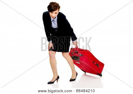 Tired and exhausted businesswoman with suitcase.