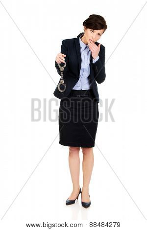 Guilty businesswoman holding metal handcuffs.