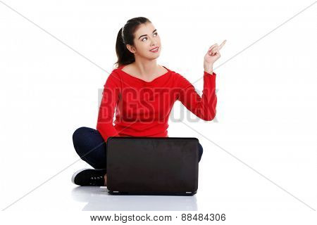 Woman sitting cross-legged pointing up.