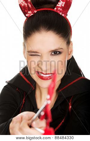 Beautiful woman in devil carnival costume blinks eye.