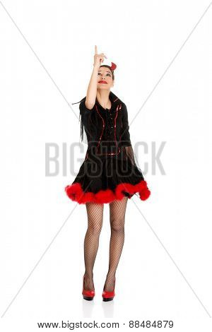 Beautiful woman in devil carnival costume pointing up.
