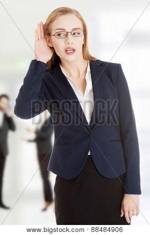 Surprised businesswoman overhears a conversation.