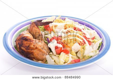 Colorful salad with chicken thigh and wing on the side, on plate with light background