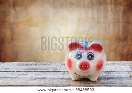 Piggy Bank On Wooden Table Over Blurred Grunge Background  Background.