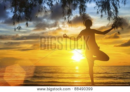 Young woman practicing yoga on the beach at sunset.