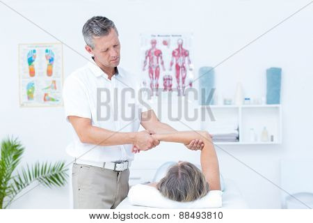 Physiotherapist examining his patients arm in medical office