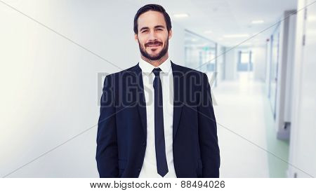 Smiling businessman in suit standing with hands in pockets against college hallway