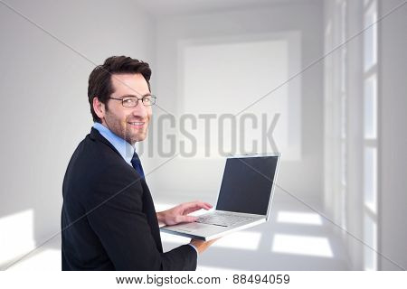 Smiling businessman using a laptop against white room with square at wall