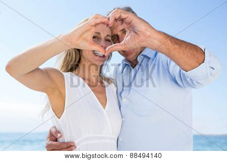 Happy couple smiling at camera and doing heart shape with their hands at the beach
