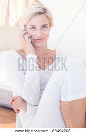 Smiling blonde woman calling on the phone in her bedroom