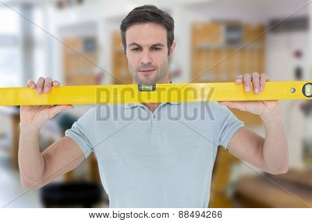 Repairman holding spirit level against workshop