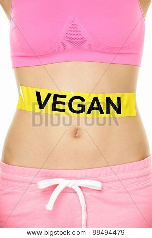 Vegan diet concept - word VEGAN written yellow label applied on woman stomach to show a vegetarian eating style. Closeup of female lower body for lifestyle concept.