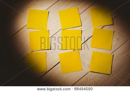 Yellow post its on wooden backround