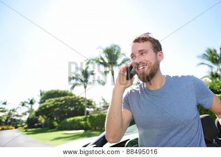 Urban smart casual young business man talking on smartphone next to his car on a summer day. Happy male adult speaking on mobile phone coming out of his luxury convertible new or rental automobile.