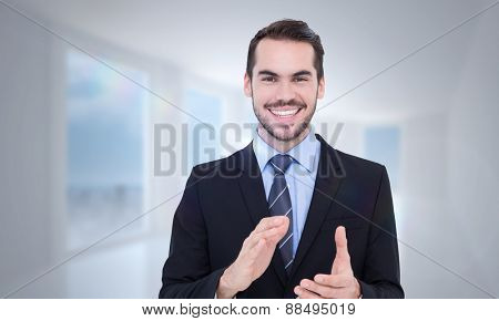 Happy businessman standing and applauding against bright white hall with columns