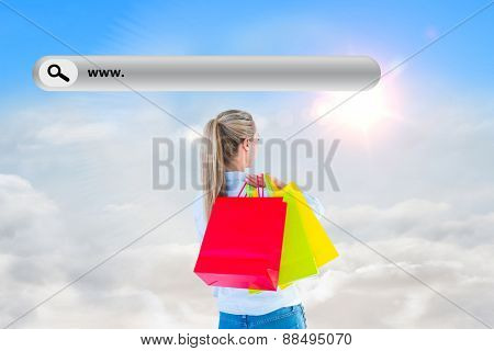 Pretty blonde holding shopping bags against blue sky with white clouds