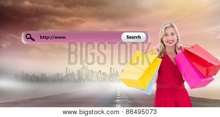 Stylish blonde in red dress holding shopping bags against large city on the horizon
