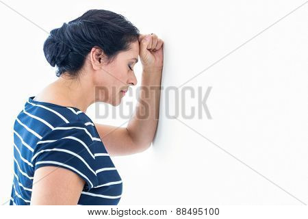 Sad woman leaning against the wall on white background