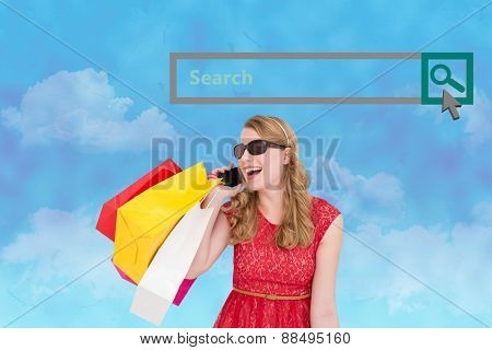 Pretty blonde talking on phone holding shopping bags against painted sky