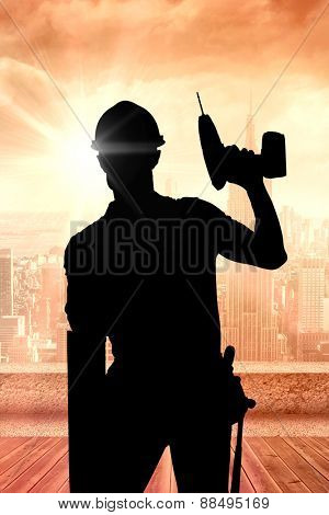 Carpenter showing thumbs up while holding drill machine against sun shining over city