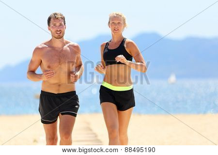 Fitness running couple exercising cardio on beach. Attractive sexy fit young adults jogging together during summer day sweating under the sun wearing black shorts and sports bra. Weight loss concept.