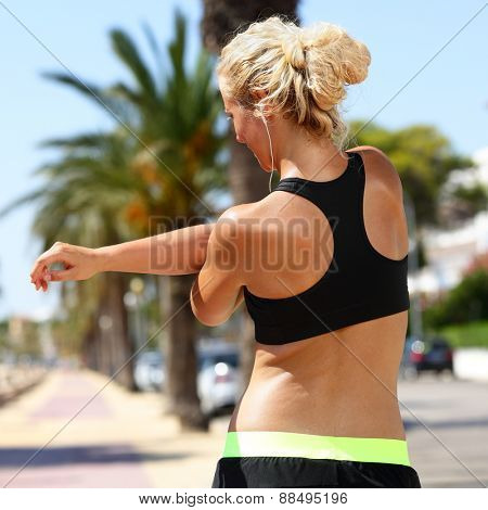 Sport female runner stretching arms before running. Woman in fitness sports bra view from the back doing stretching exercises for the shoulder muscles before a cardio workout in summer outdoors.