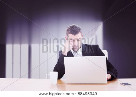 Businessman using laptop against abstract room