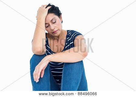 Unhappy woman sitting on the floor on white background