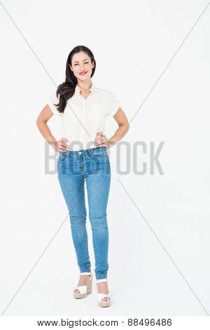 Smiling brunette standing hands on hips on white background
