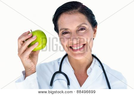 Confident female doctor holding green apple on white background