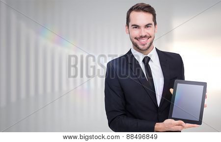 Smiling businessman showing his tablet pc against white curved room