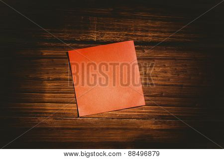 Red post it on wooden background