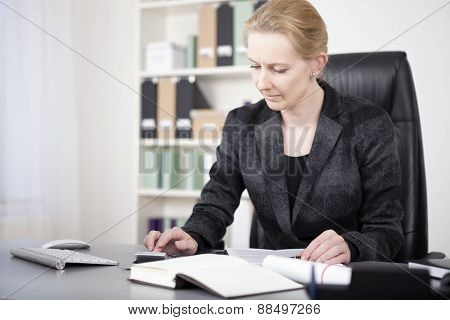 Office Woman Sitting At Her Desk Calculating Sales