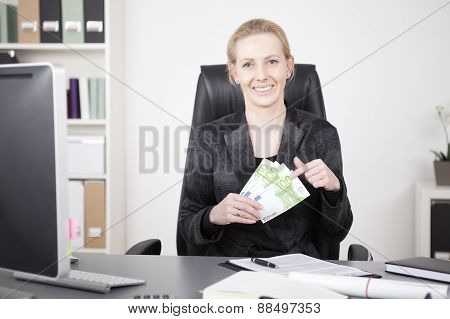 Happy Manageress At Her Desk Holding A Fan Of Cash