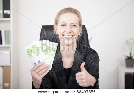 Happy Businesswoman In Thumbs Up Holding Cash