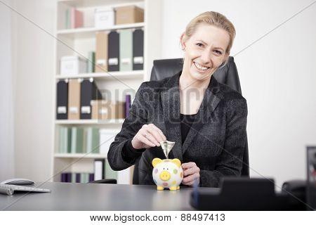 Happy Businesswoman Putting Money On Piggy Bank
