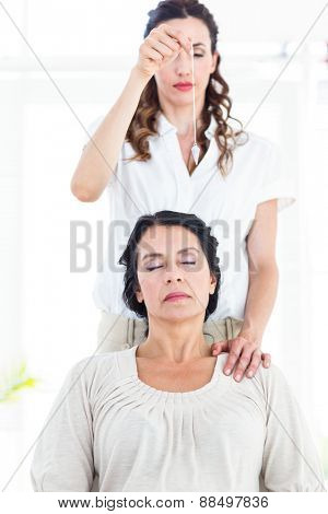 Therapist hypnotizing her patient on white background