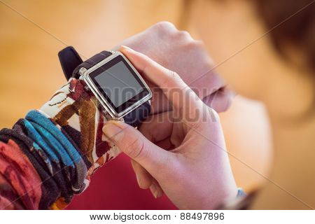 Slim woman using her smartwatch on brown background